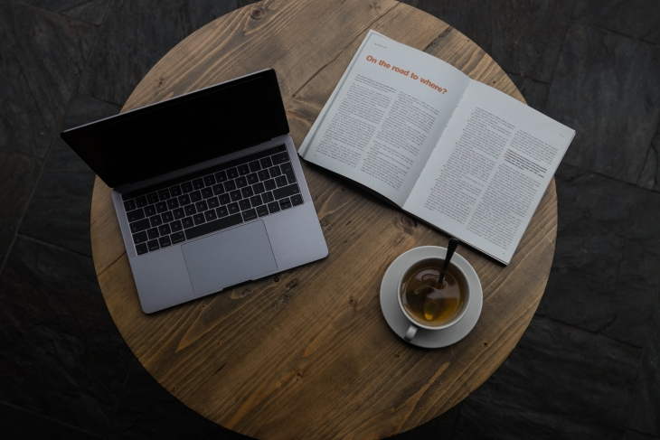 1 ordinateur portable ouvert + 1 magazine ouvert + 1 tasse de café pleine sur 1 petite table ronde en bois