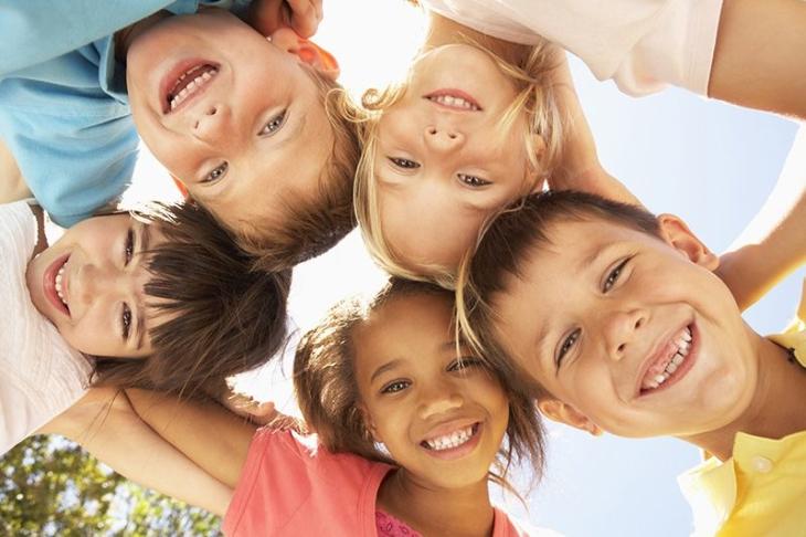 cinq enfants se tiennent par les épaules et regadent en souriant l'appareil photo qui les prend en vue de dessous.